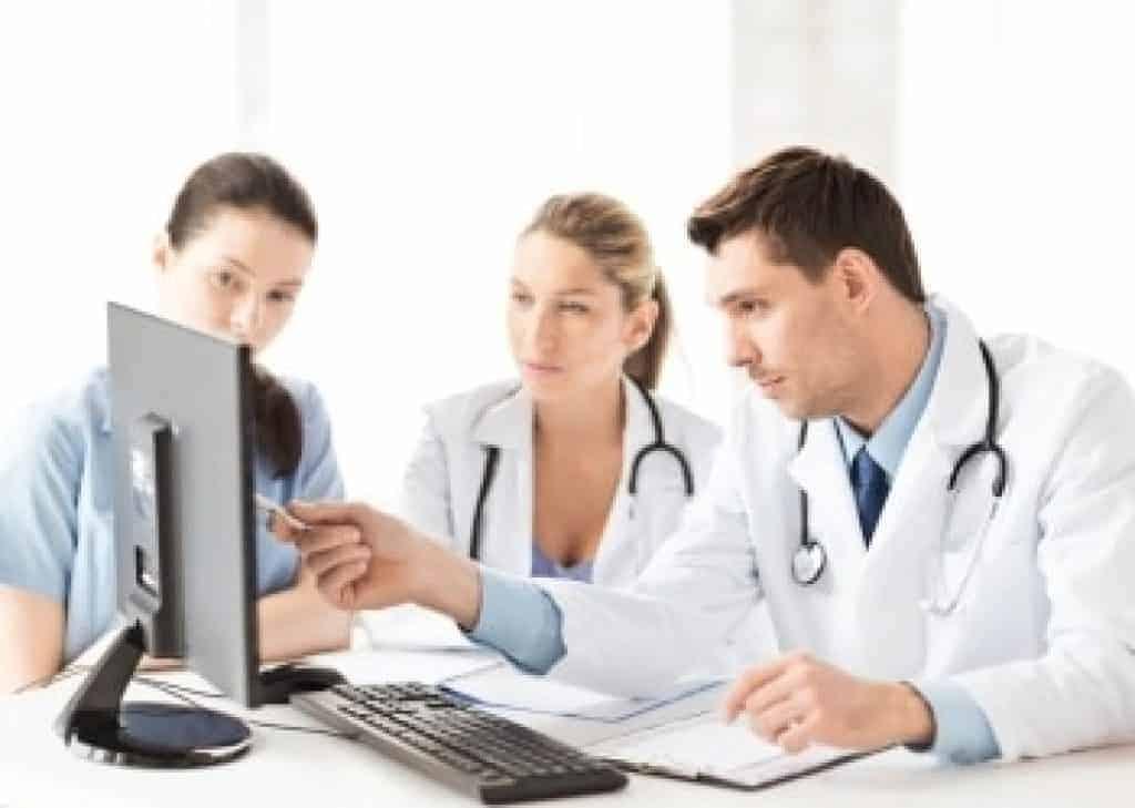 3 mladší zdravotníci spolupracující s počítačem