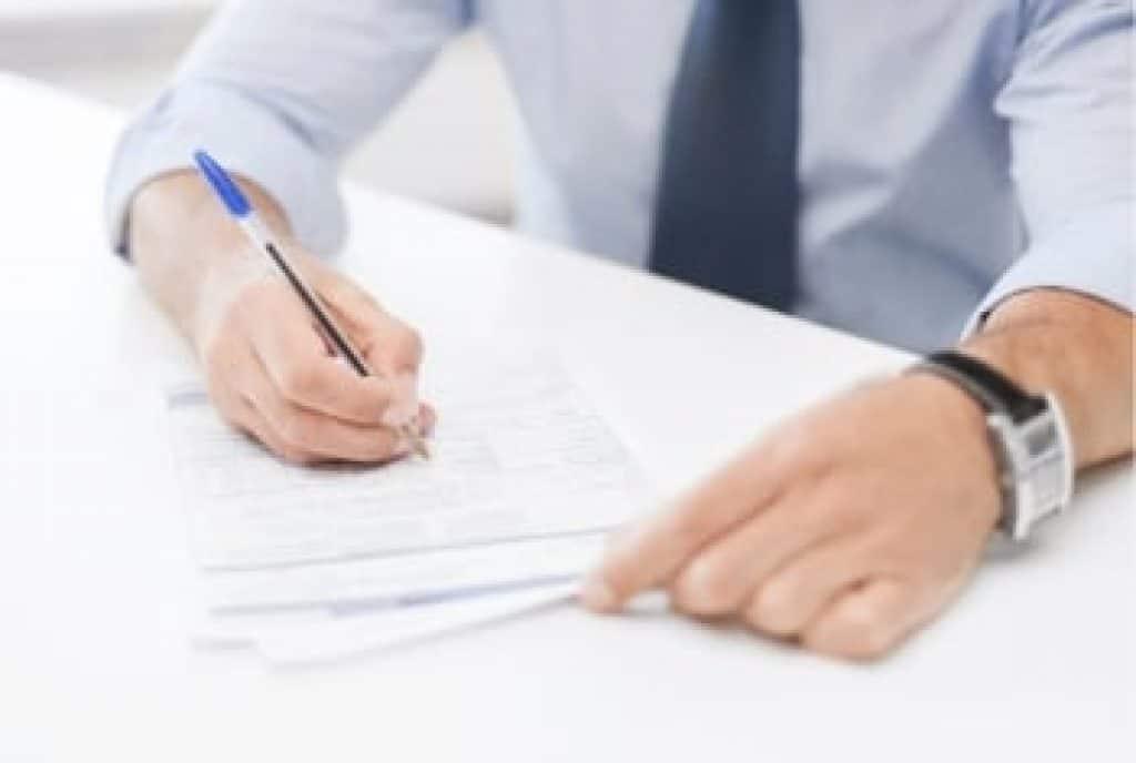mužské ruce při podpisu smlouvy
